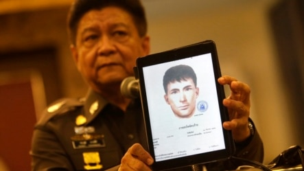 Police spokesman Lt. Gen. Prawuth Thavornsiri shows a photo of one of three men that Thai authorities have issued new arrest warrants in connection with the bombing case, bringing the total number of wanted suspects to seven during a press conference in Bangkok, Thailand, Tuesday, Sept. 1, 2015. Thai authorities arrested a man they believe is part of a group responsible for a deadly bombing at a shrine in central Bangkok two weeks ago, Prime Minister Prayuth Chan-ocha announced Tuesday. He said the suspect resembles a yellow-shirted man in a surveillance video who police say planted the bomb. (AP Photo/Sakchai Lalit)