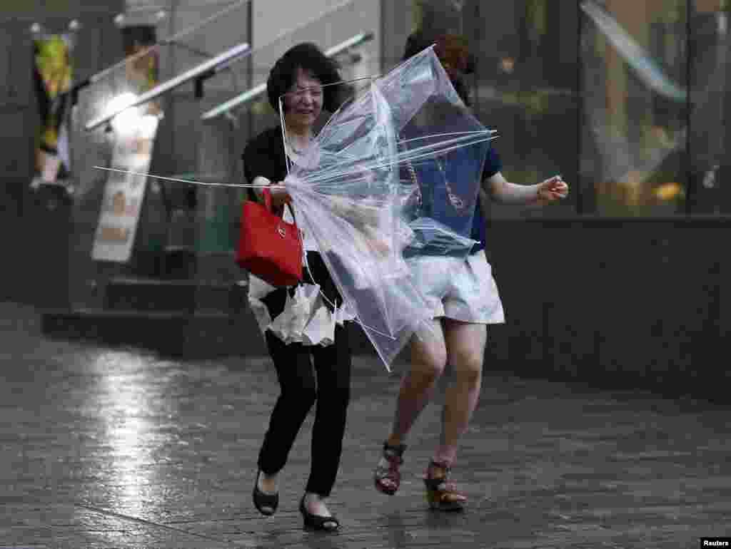 当地时间8月10日,受台风夏浪影响,日本东京刮起强风下了暴雨。据报道,台风夏浪已在日本造成一人死亡,33人受伤。日本有关部门已疏散西部台风沿线160万居民。图为东京街头几名女性在暴风雨中艰难行进。