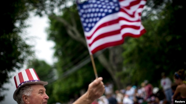 FILE - A man waves an American flag as he watches a July Fourth parade in the village of Barnstable, Massachusetts, July 4, 2014.