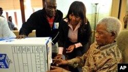 Presidente Mandela a votar esta Segunda-feira em Joanesburgo com o apoio de uma das suas netas