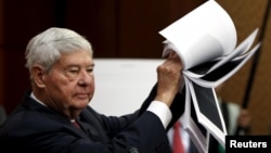 FILE - Former Senator Bob Graham (D-FL) displays 28 pages that are still classified and blacked out, of a U.S. government report on who financed the 9/11 attacks on the United States, at a news conference on Capitol Hill, July 5, 2015.