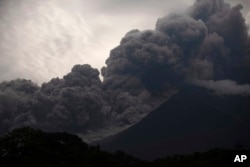 Volcan de Fuego, or Volcano of Fire, blows outs a thick cloud of ash, as seen from Alotenango, Guatemala, Sunday, June 3, 2018. (AP Photo/Santiago Billy)