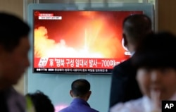 People watch a TV news program showing a file image of a missile launch conducted by North Korea, at the Seoul Railway Station in Seoul, South Korea, May 14, 2017. A missile was fired from near Kusong in North Phyongan province.