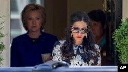 Asisten dekat Hillary Clinton, Huma Abedin, berjalan mendahului kandidat presiden AS dari Partai Demokrat itu rumah Clinton di Washington. (Foto: Dok)