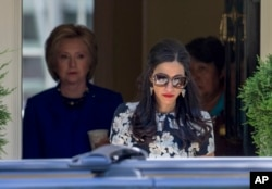FILE - Top Clinton aide Huma Abedin walks ahead of Democratic presidential candidate Hillary Clinton at Clinton's home in Washington, June 10, 2016.