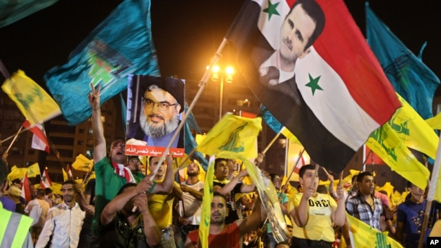 Hezbollah supporters wave flags and pictures of Syrian President Bashar al-Assad and Hezbollah leader Sheik Hassan Nasrallah during a rally marking the sixth anniversary of the 2006 Israel-Hezbollah war, in Beirut, July 18, 2012.
