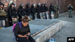 A woman checks her phone while police officers monitor the situation near a pharmacy that was looted and burned by rioters on Monday after the funeral of Freddie Gray, on April 29, 2015, in Baltimore, Maryland.