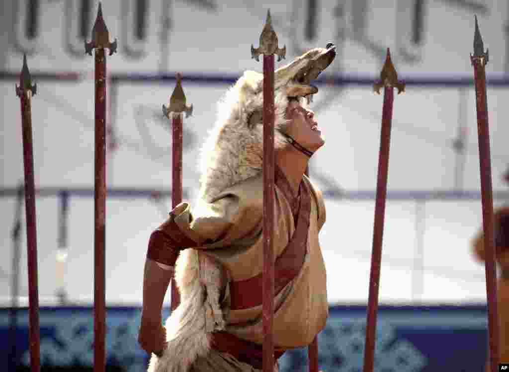 Một người đội lốt sói biểu diễn trong Lễ hội Naadam ở Ulaanbaatar, Mông Cổ. Mông Cổ kỷ niệm cuộc hành quân của Thành Cát Tư Hãn chinh phục thế giới vào ngày 11 tháng 7, với lễ hội thể thao Naadam hàng năm bao gồm những sự kiện thể thao truyền thống của Mông Cổ như đấu vật, bắn cung, và đua ngựa.