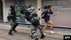 Cảnh sát truy đuổi hai người biểu tình đeo khẩu trang ở khu Trung Hoàn của Hong Kong, một ngày sau khi lãnh đạo của thành phố ban hành lệnh cấm đeo khẩu trang để ứng phó với các cuộc biểu tình ngày càng bạo lực, ngày 5 tháng 10, 2019.