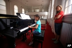 Vicky Chavez watches her daughter Yaretzi play on the piano in the chapel of the First Unitarian Church in Salt Lake City, Utah, May 31, 2018.