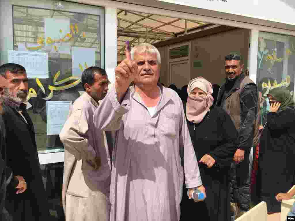 បុរសម្នាក់បង្ហាញម្រាមដៃដែលមានជាប់ទឹកខ្មៅ បន្ទាប់ពីបោះឆ្នោតនៅក្នុងជំរំជនភៀសខ្លួន Khazir ខាងកើតក្រុង Mosul ប្រទេសអ៊ីរ៉ាក់ កាលពីថ្ងៃទី១២ ខែឧសភា ឆ្នាំ២០១៨។