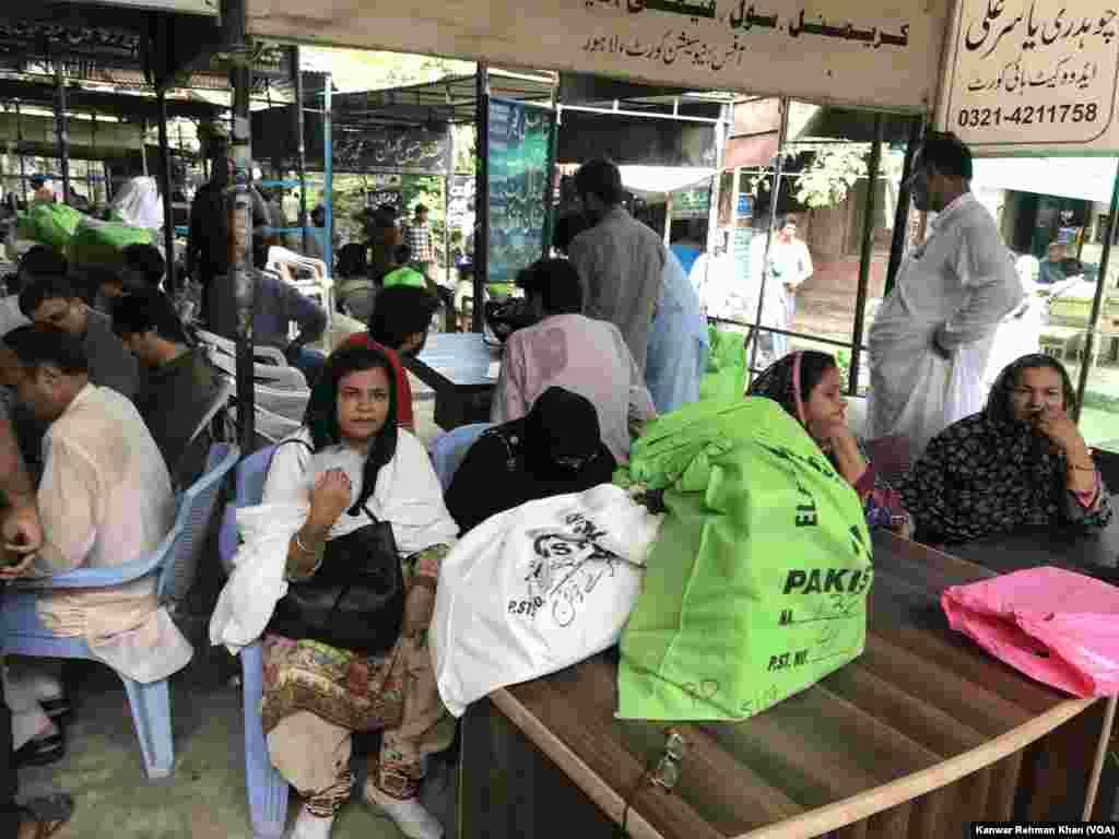 خواتین پریزائڈنگ افسران سامان وصول کرنے کے بعد لاہور کی سیشن عدالت میں بیٹھی ہوئی ہیں۔