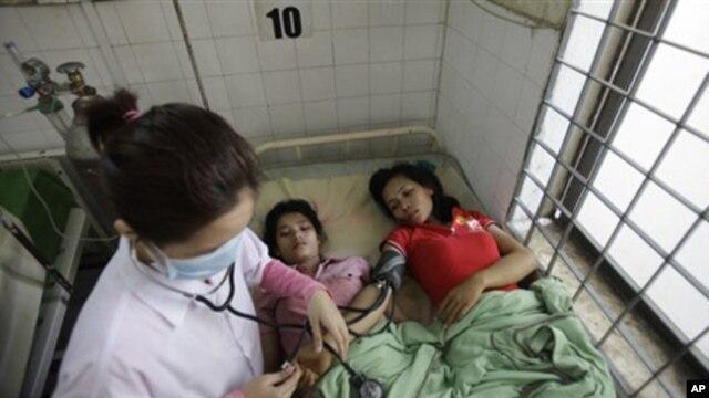 A Cambodian doctor checks blood pressure of survivors of the Nov. 22 bridge stampede at Preah Kossamak Hospital in Phnom Penh.