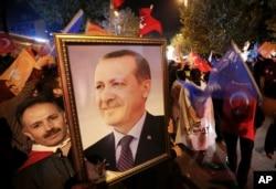 ຜູ້ສະໜັບສະໜູນພັກ ຍຸດຕິທຳ ແລະ ການພັດທະນາ ຫຼຶ AKP ຖືຮູບຂອງປະທານາທິບໍດີ ເທີກີ ທ່ານ Recep Tayyip Erdogan ໃນຂະນະທີ່ປະຊາຊົນພາກັນສະເຫຼີມສະຫຼອງຢູ່ນອກສຳນັກງານໃຫຍ່ຂອງພັກ AKP ໃນນະຄອນ ອິສຕານບູລ, ເທີກີ, ຕອນແລງວັນອາທິດ ທີ 1 ພະຈິກ 2015.