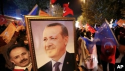 ຜູ້ສະໜັບສະໜູນພັກຍຸດຕິທຳ ແລະ ການພັດທະນາ (AKP) ຖືຮູບພາບ ຂອງປະທານາທິບໍດີ Recep Tayyip Erdogan ຢູ່ທີ່ການສະເຫຼີມສະຫຼອງ ໄຊຊະນະ ຢູ່ນອກສຳນັກງານໃຫຍ່ຂອງພັກໃນນະຄອນ Istanbul, ປະເທດເທີກີ, ວັນທີ 1 ພະຈິກ 2015.