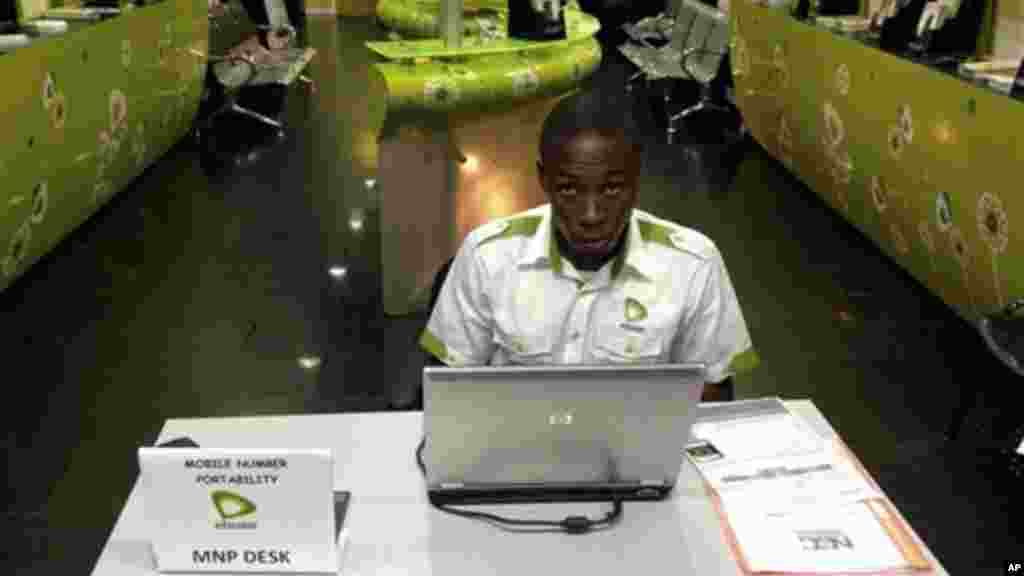 In this photo taken on an iphone, a staff member of Etisalat Nigeria waits for customers, during the launch of mobile number portability in Lagos, Nigeria, Monday, April 22, 2013.