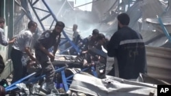 An image made from video posted online by the Shaam News Network, a loosely organized group opposed to Bashar Assad, Aug. 16, 2015, which has been verified and is consistent with other AP reporting, shows rescuers taking a victim from the site of Syrian government airstrikes in Douma.