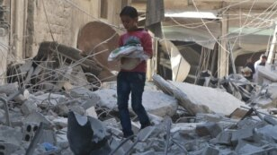 A boy carries bread as he makes his way through rubble of a site hit by an airstrike in the rebel-held area of Aleppo's al-Sukari district, Syria, May 30, 2016.
