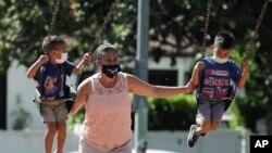 미 로스앤젤레스의 한 놀이터에서 마스크를 쓴 가족이 그네를 타고 있다.(자료사진)