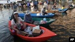 一个卖鸡蛋的小贩11月17日在曼谷郊外一个被洪水淹没的市场上