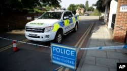 A British police vehicle stands parked next to an area which was extended overnight to include the Lush House car park adjacent to the Queen Elizabeth Gardens park in Salisbury, England, Thursday, July 5, 2018. The area has been linked to what is believed to be another chemical incident involving a nerve agent.