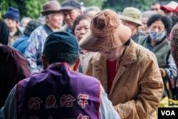 台湾人安基金会的工作人员对申请者做简单的身份识别后即送出午餐邀请单。(美国之音记者方正拍摄)