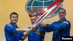 俄美日三名宇航員在拜科努爾航天基地升空前與奧運火炬合影。
