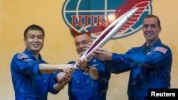 Phi hành gia Nhật Bản Koichi Wakata, nhà du hành vũ trụ Nga Mikhail Tyurin, và phi hành gia Mỹ Rick Mastracchio, chụp ảnh cùng với ngọn đuốc Olympic 2014