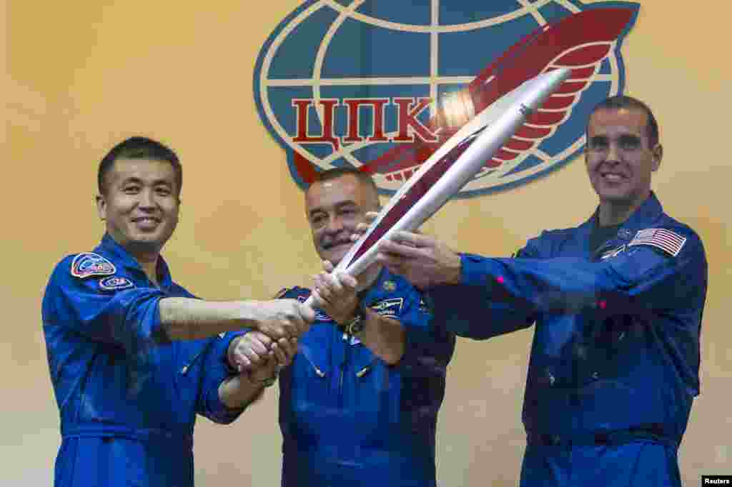 International Space Station crew members, Japanese astronaut Koichi Wakata, Russian cosmonaut Mikhail Tyurin and U.S. astronaut Rick Mastracchio, pose with the torch of the 2014 Sochi Winter Olympic Games after a news conference behind a glass wall at the