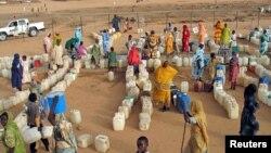 Des femmes soudanaises déplacées à l'intérieur du pays font la queue pour remplir des conteneurs d'eau dans le camp d'Abu Shouk dans la province du Darfour au Soudan.