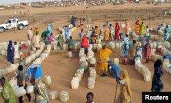 دارفر کے ایک پناہ گزین کیمپ میں عورتیں پانی بھرنے کے لیے اپنی باری کا انتظار کررہی ہیں۔