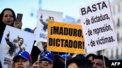 """La gente sostiene pancartas que dicen """"Maduro, dictador!"""" y """"Basta de dictadura, represión y víctimas"""" durante una manifestación convocada por ciudadanos venezolanos contra el presidente Nicolás Maduro, en Madrid."""