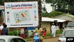 People walk in front of posters for the presidential elections and instructions on the voting card, Conakry, Guinea, 25 Jun 2010