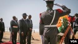 Le président ivoirien Alassane Ouattara se prépare à déposer une couronne de fleurs en mémoire des personnes tuées dans l'attaque jihadiste sur une plage de Grand Bassam, 16 mars 2016. (E. Iob / VOA)
