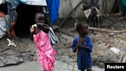 Children walk through mud in an internally displaced persons camp inside the United Nations base in Malakal, South Sudan, July 23, 2014.