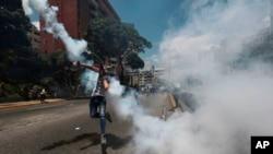 Un manifestante arroja una granada de gas lacrimógeno lanzada por la Policía Nacional Bolivariana durante una manifestación en Caracas, Venezuela, el sábado 8 de abril de 2017.