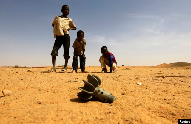 FILE - Children look at the fin of a mortar projectile that was found at the Al-Abassi camp for internally displaced persons, after an attack by rebels, in Mellit town, North Darfur, March 25, 2014.