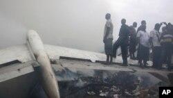 Warga berdiri di dekat reruntuhan pesawat yang jatuh di kota Lagos, Nigeria hari Minggu (3/6). Seluruh 153 penumpang dan awak pesawat dilaporkan tewas.