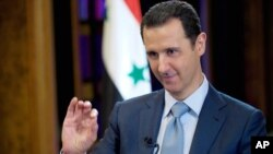 FILE - In this Feb. 10, 2015 photo released by the Syrian official news agency SANA, Syrian President Bashar Assad gestures during an interview with the BBC, in Damascus.