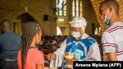 Une catholique reçoit la Sainte Communion à la cathédrale Notre-Dame du Congo à Kinshasa le 16 août 2020 lors de la première messe célébrée depuis le 24 mars, en raison de la pandémie COVID-19.