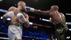 Floyd Mayweather Jr. jabs Conor McGregor in a super welterweight boxing match, Aug. 26, 2017, in Las Vegas.