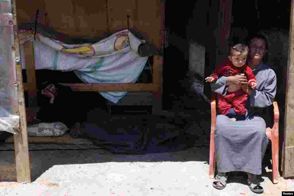 Syrian refugees sit outside their home in a refugee camp in the eastern Lebanese town of Anjar near the Syrian border, May 13, 2014.