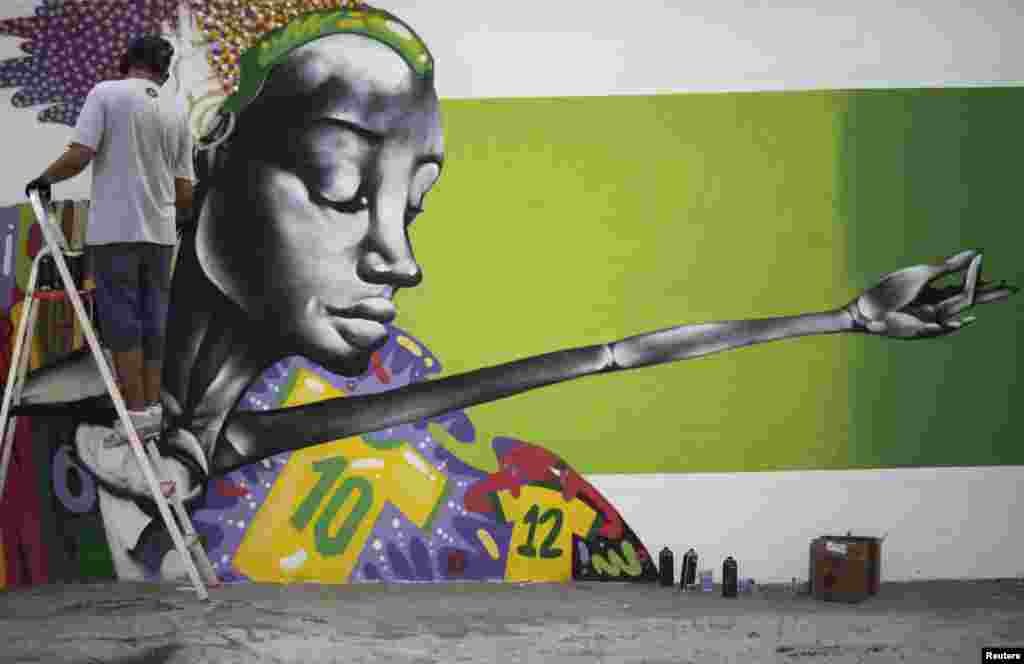 Graffiti artist Barba works on a mural in celebration of the 2014 soccer World Cup in Rio de Janeiro, Brazil. The mural will be a part of a contest organized by city hall.