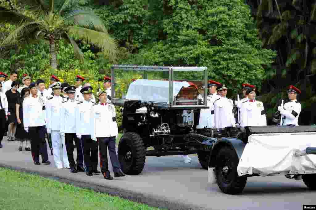 Pasukan Kehormatan mengawal peti jenazah perdana menteri pertama Singapura yang akan dibawa ke Gedung Parlemen tempat ia akan disemayamkan sampai Sabtu di Singapura (25/3).