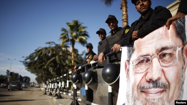 Policemen stand guard near a poster outside the constitutional court put up by supporters of Egyptian President Mohamed Morsi as they stage a sit-in, in Cairo, December 23, 2012.