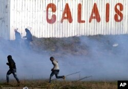 Migrants run away from tear gas thrown by police forces near the Channel Tunnel in Calais, northern France, Jan.21, 2016