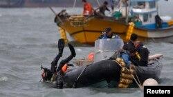 Seorang penyelam terjun ke laut mencari para penumpang kapal Korea Selatan yang tenggelam di Jindo (21/4). (Reuters/Kim Hong-ji)