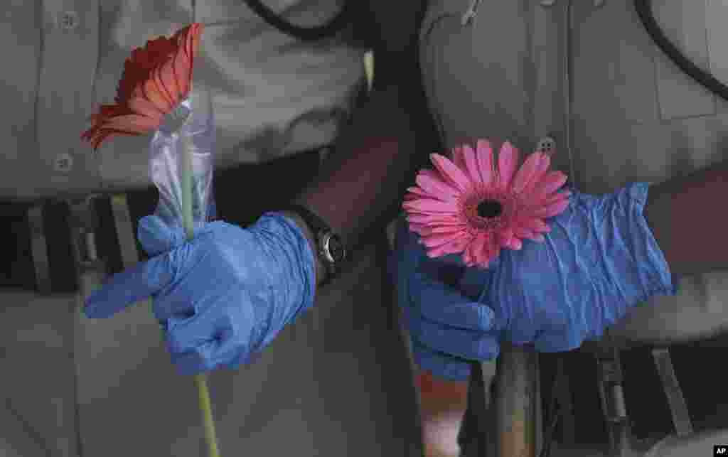 Security officers hold flowers given to them as a show of thankfulness at the end of a free medical camp in the extremely poor area of Dharavi, in Mumbai, India.