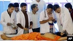 A doctor inspects the health of Indian yoga guru Baba Ramdev at Ramdev's ashram in Haridwar, India, June 10, 2011.