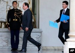 French President Francois Hollande, center, and Prime Minister Manuel Valls, right, walk through the lobby of the Elysee Palace after the weekly cabinet meeting, in Paris, Nov. 18, 2015.